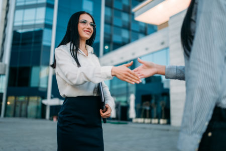 Business woman in glasses and white blouse, handshake with partner outdoor. Modern building, financial center. Successful female businessperson